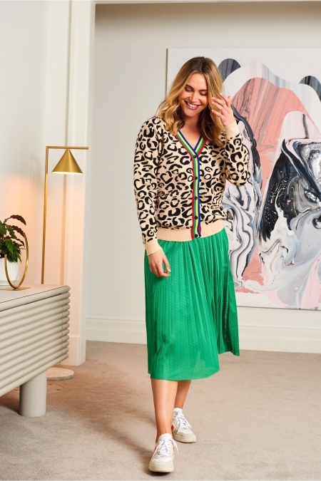 Marley Cardigan on a model with green skirt in an apartment